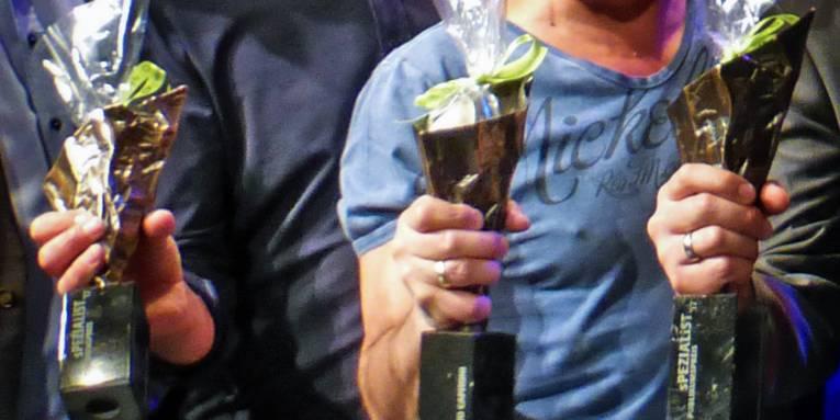 Drei Personen halten je einen Pokal in den Händen