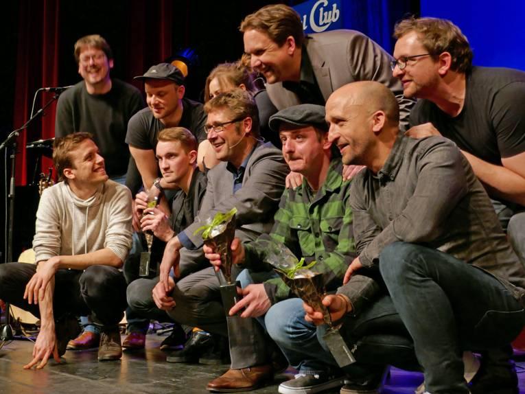 Menschen knien auf einer Bühne zum Gruppenfoto.