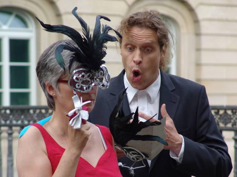 Mann singt zu einer Frau mit Maske.