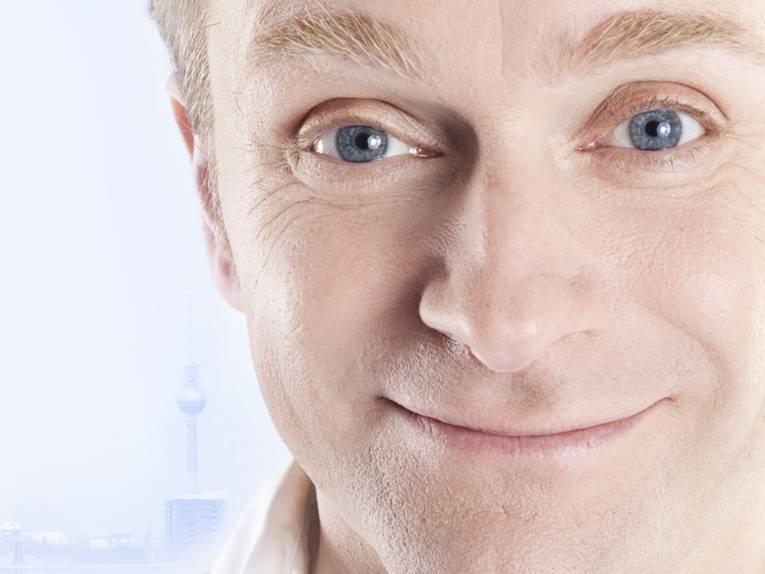 Nahaufnahme eines lächelnden Mannes mit blauen Augen.