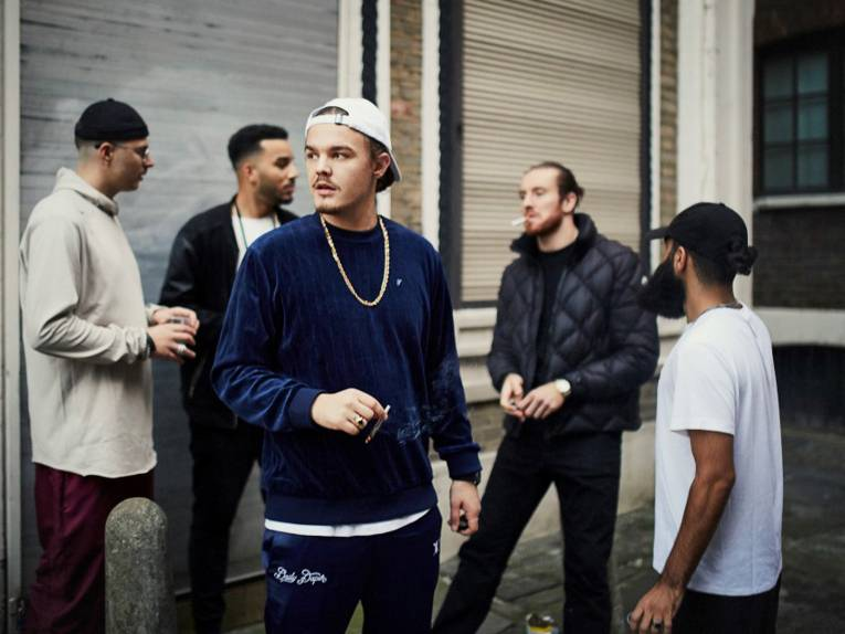 Ein junger Mann steht mit einer Gruppe an einer Straßenecke und raucht einen Joint.
