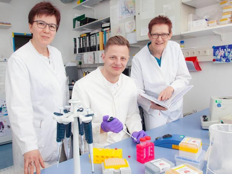 Zwei Frauen und ein Mann in weißen Kitteln an einem Labortisch