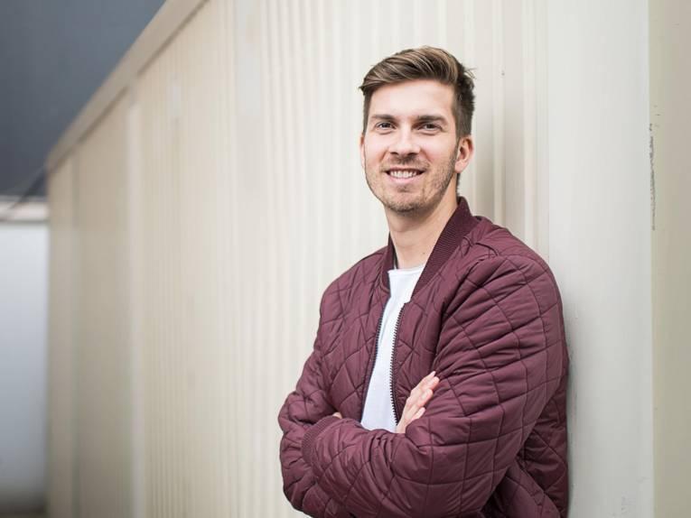 Ein lächelnder junger Mann mit Dreitagebart.