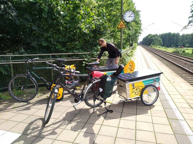 Mann mit zwei Fahrrädern mit Anhängern an einem Bahnsteig