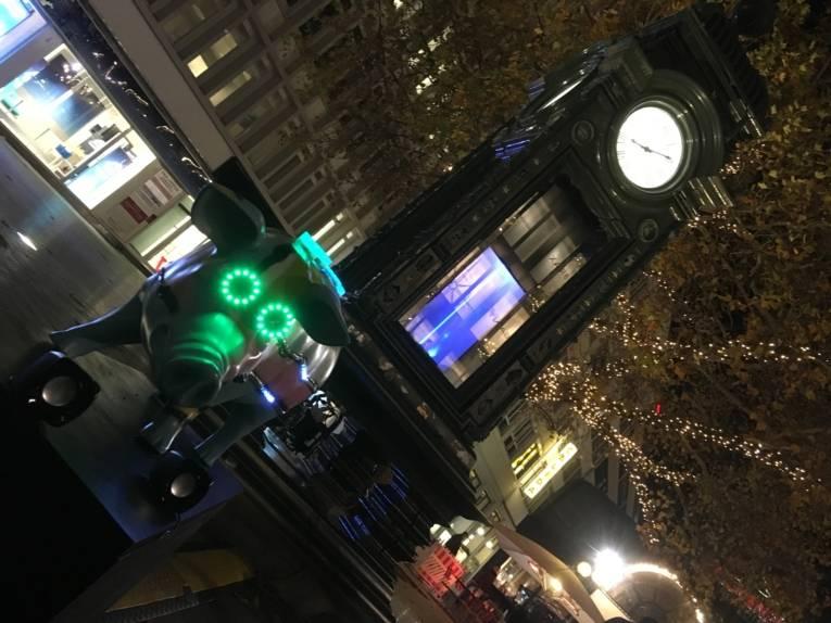 Standuhr, davor steht eine Skulpur in Form eines Schweins mit grün leuchtenden Augenringen
