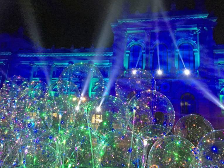Blau angestrahltes Gebäude, davor durchsichtige Blasen