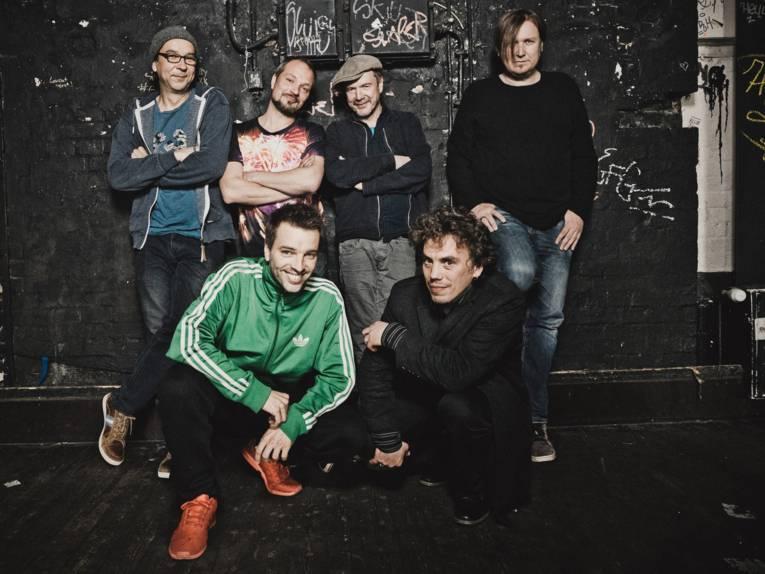 Sechs lächelnde Männer vor einer mit hellen Schriftzügen beschmierten schwarzen Wand