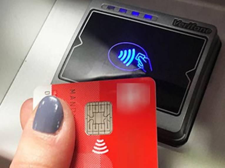 Hand hält eine EC-Karte vor ein Lesegerät zur kontaktlosen Zahlung