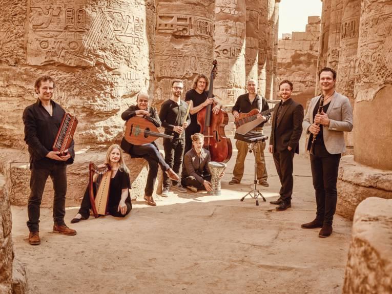 Gruppe von Musikern in der Wüste zwischen alten Sandstein-Säulen