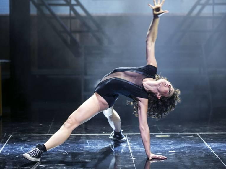 Frau in akrobatisch-tänzerischer Pose auf dem Boden einer Bühne
