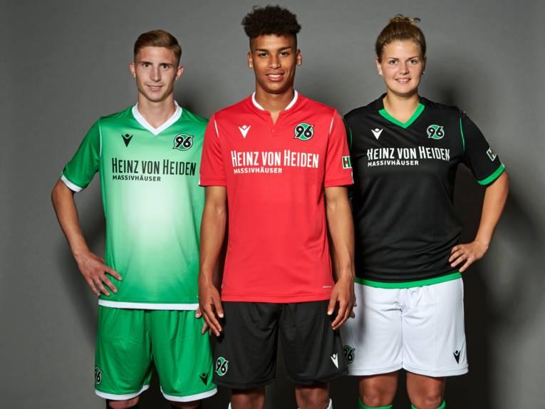 Zwei Männer und eine Frau in Fußballkleidung