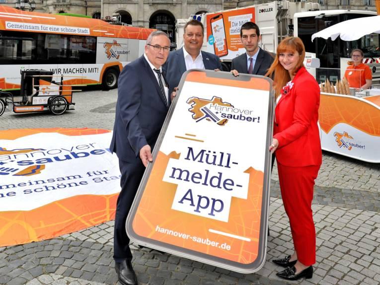 """Drei Männer und eine Frau halten ein riesiges Handy, auf dem der Schriftzug """"Müllmelde-App"""" zu sehen ist."""