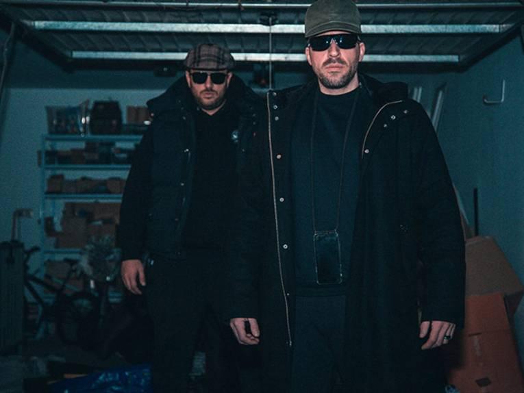 Zwei Männer stehen mit Sonnenbrille in einer dunklen Garage