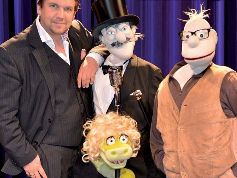 Ein Mann im Anzug mit drei Puppen