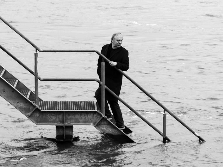 Ein Schwarz-Weiß-Bild. Darauf ein Mann auf einem Steg. Im Hintergrund ist Wasser.