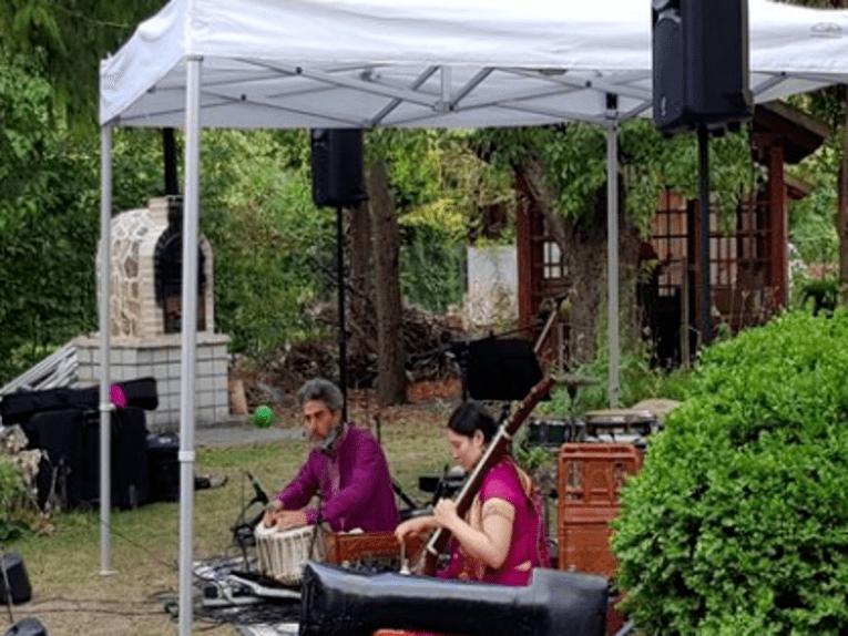 Mann und Frauen sitzen draußen und spielen ein Instrument