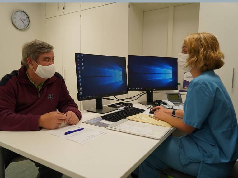 Eine Frau und ein Mann mit Masken sitzen sich an einem Schreibtisch gegenüber.