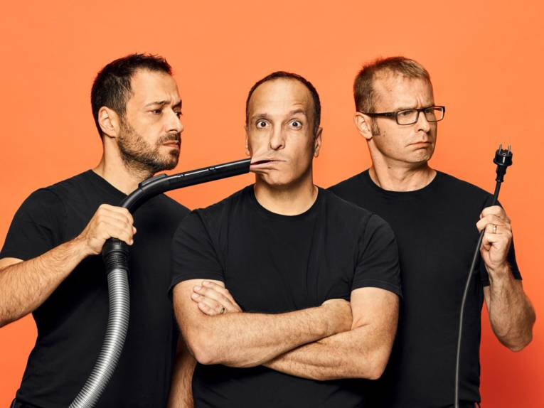 Drei Männer, wovon einer mit dem in der Mitte einen Staubsauger an die Wange hält.