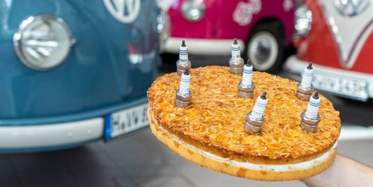 Kuchen mit Zündkerzen vor Fahrzeugen
