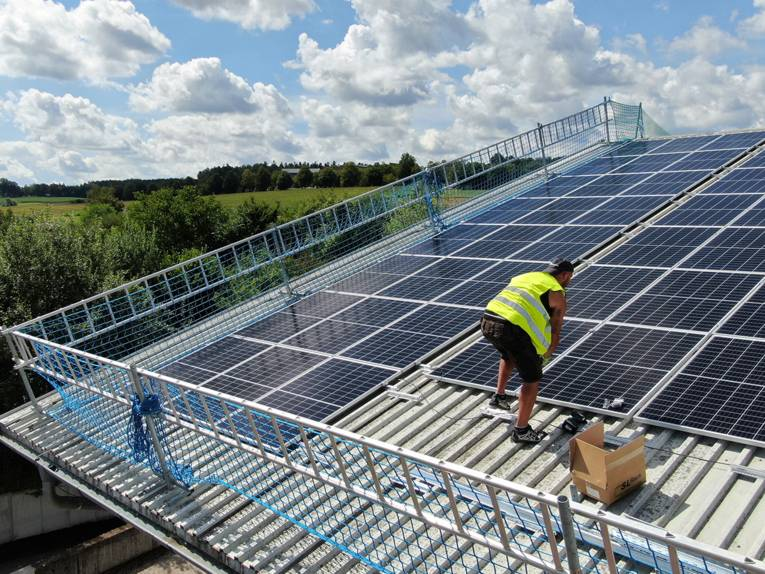 Arbeiter auf einem Dach mit Sonnenkollektoren