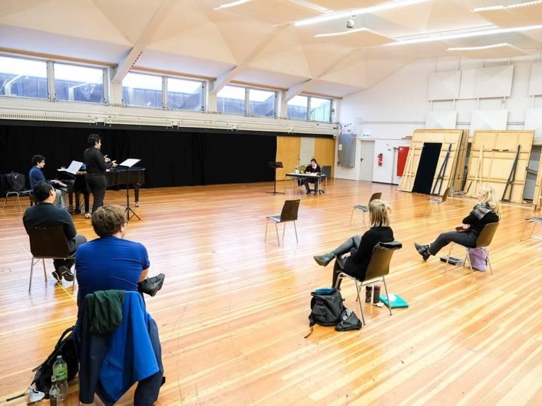 Künstler sitzen auf Stühlen in einem großen Saal.
