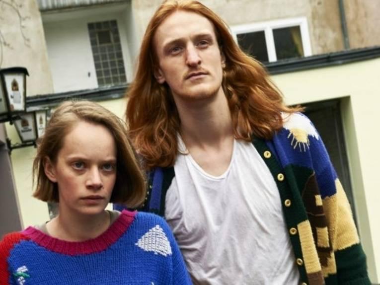 Eine Frau und ein Mann stehen nebeneinander mit ernstem Gesicht.