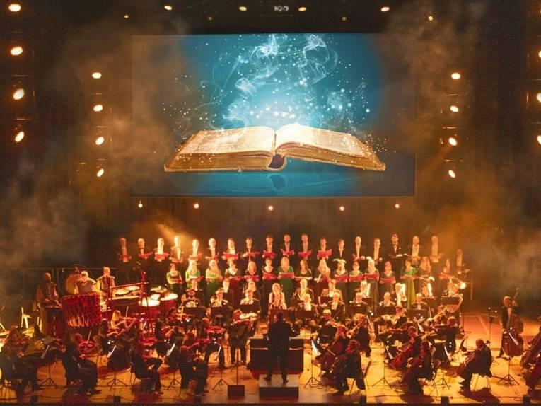 Auf einer Bühne steht ein Orchester mit einem Chor. Über ihnen hängt eine Leinwand mit einem geöffneten Buch drauf.
