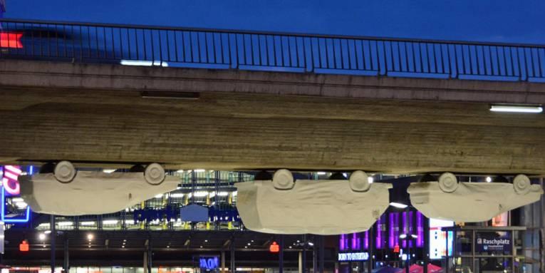 Lebensgroße Pappmachee-Autos hängen unter einer Brücke