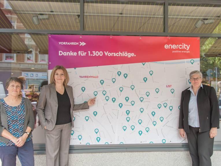 """Drei Frauen stehen vor einem großen Plakat mit der Aufschrift: """"Vorfahren. Danke für 1.300 Vorschläge"""" und einem Stadtplan."""