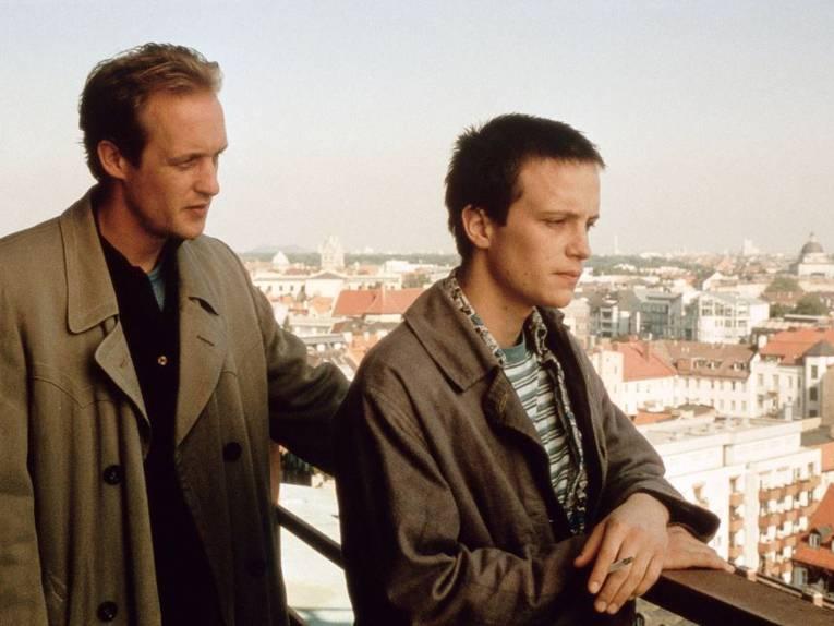 Zwei Männer auf einer Aussichtsterrasse mit Blick über eine Stadt.