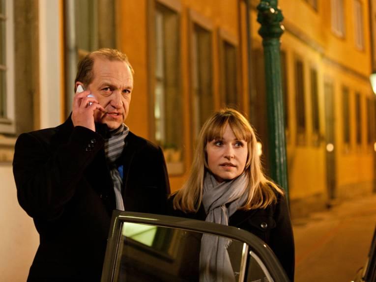 Ein Mann und eine Frau stehen an einer geöffneten Autotür, der Mann telefoniert mit einem Mobiltelefon.