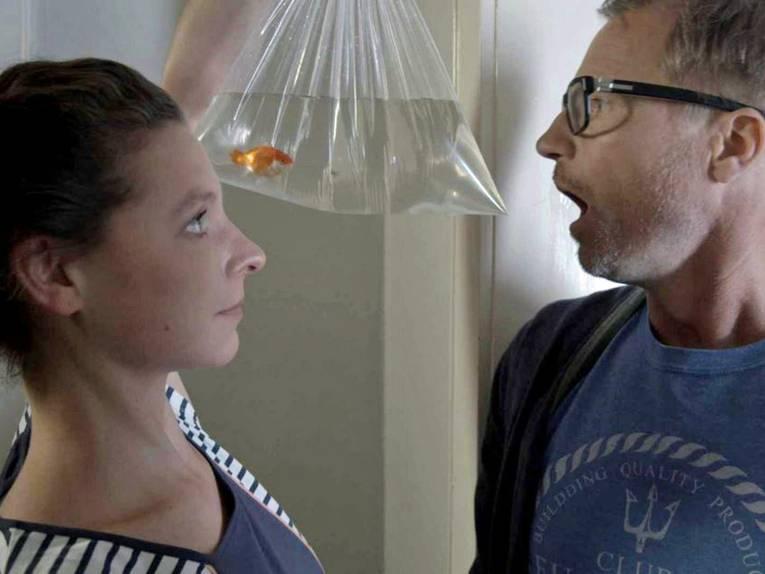 Eine Frau hält vor einem Mann einen mit Wasser und Goldfisch gefüllten Beutel in der Hand.