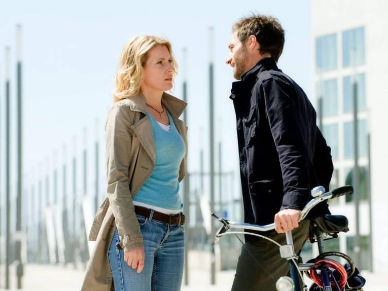 Frau und Mann mit Fahrrad auf einer großen Fußgängerbrücke.