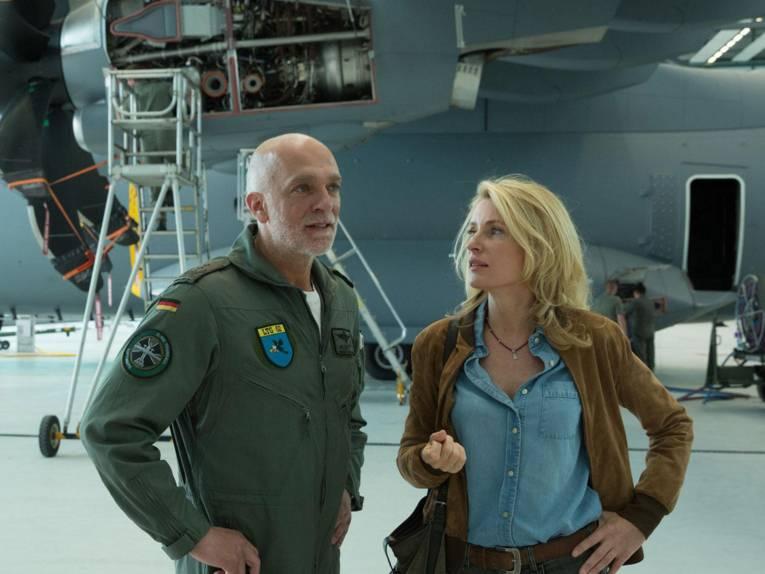Mann in Bundeswehruniforum und Frau vor einem Transportflugzeug in einer Halle