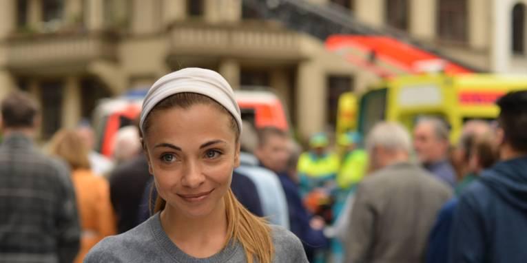 Frau im Vordergrund. Im Hintergrund erkennt man unscharf Passanten, Rettungswagen und Feuerwagen sowie Rettungskräfte