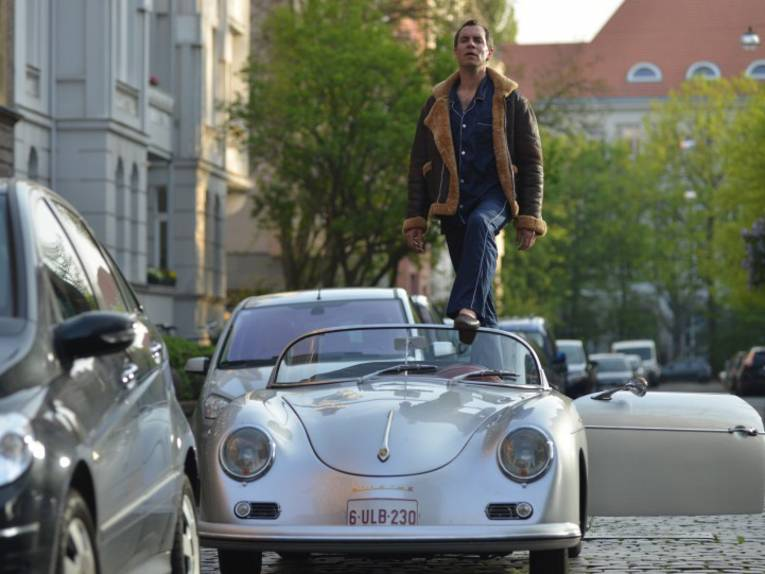 Mann steht in einem Cabriolet.