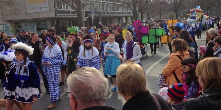 Ein Karnevalsumzug mit verkleideten Menschen und Zuschauern.