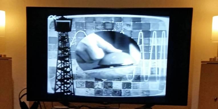 Fernsehbild in Schwarzweiß, das einen einen Daumen, der auf einen Knopf drückt, zeigt