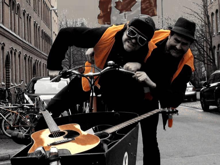 Zwei Männer mit Warnweste auf einem Lastenrad.