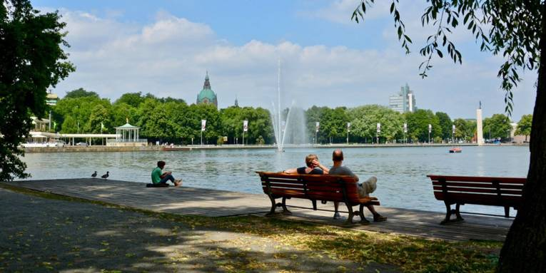 Menschen sitzen auf einem Holzsteg an einem Stadtsee.