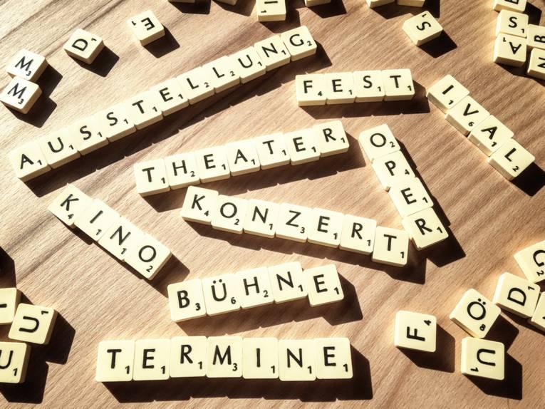 """Kleine Steine mit Buchstaben und Zahlen bilden Wörter wie """"Konzerte"""" und """"Theater""""."""