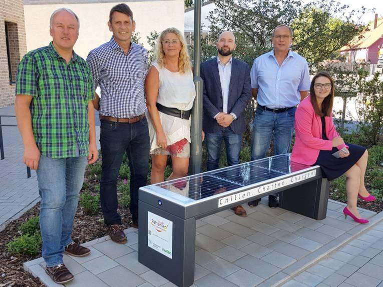 Zwei Frauen und vier Männer posieren an einer Solarbank mit der Aufschrift: Chillen. Chatten. Chargen!