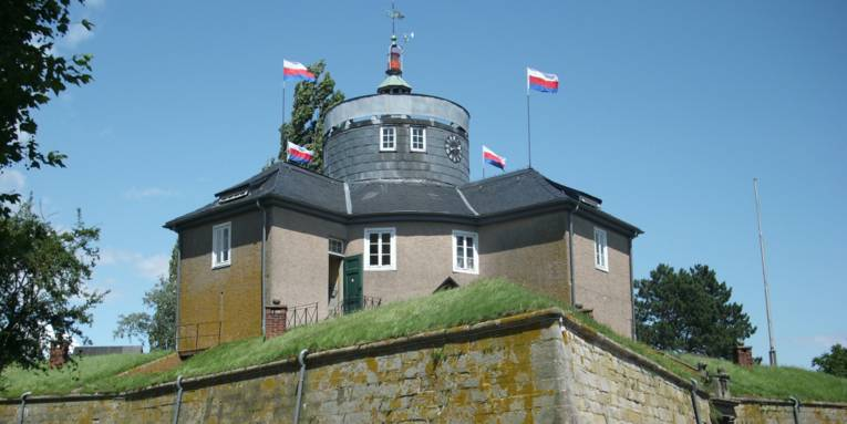 Gebäude auf einer mit Mauern befestigten Rasenfläche
