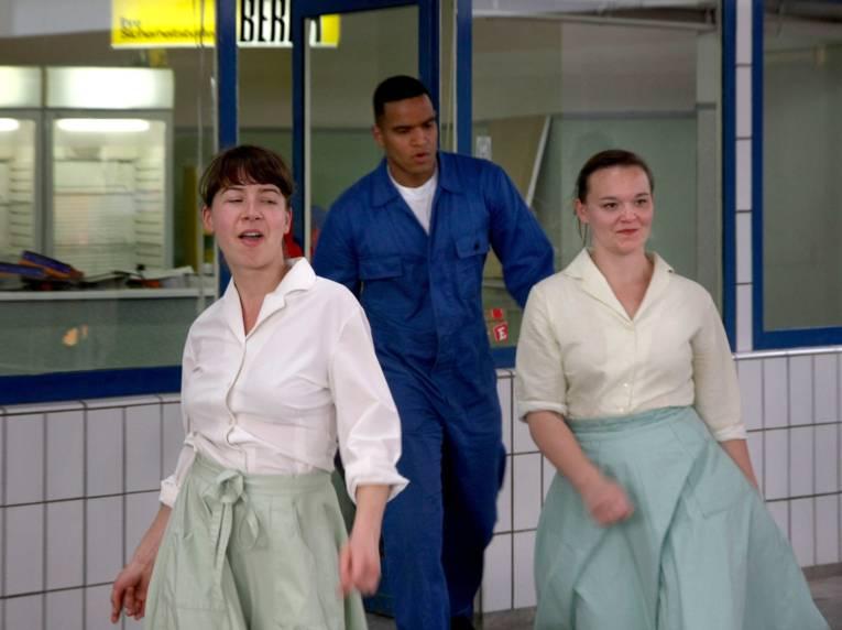 Szene aus einem Stück: Zwei Frauen in türkisen Petticoats kommen aus einer Tankstelle, ihnen folgt ein Mann im Blaumann.