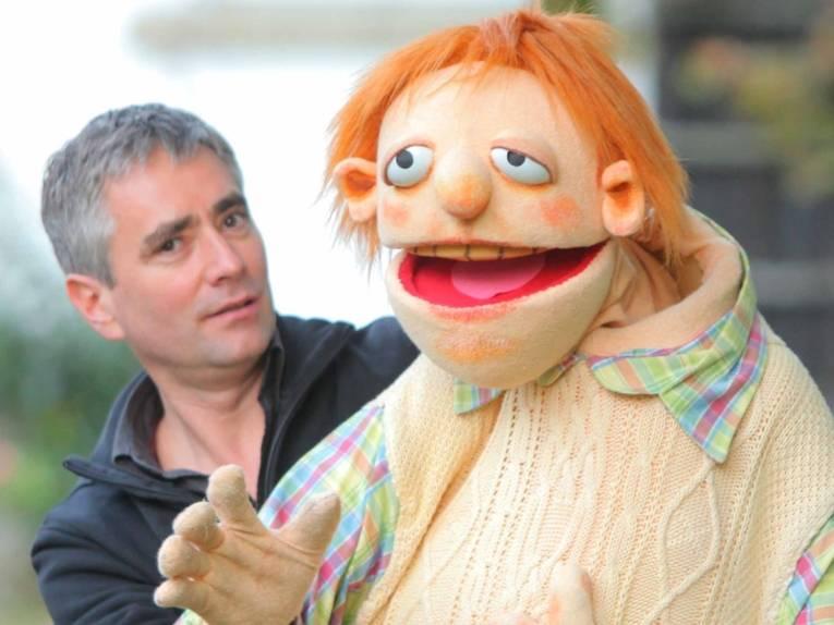 Mann mit Puppe.