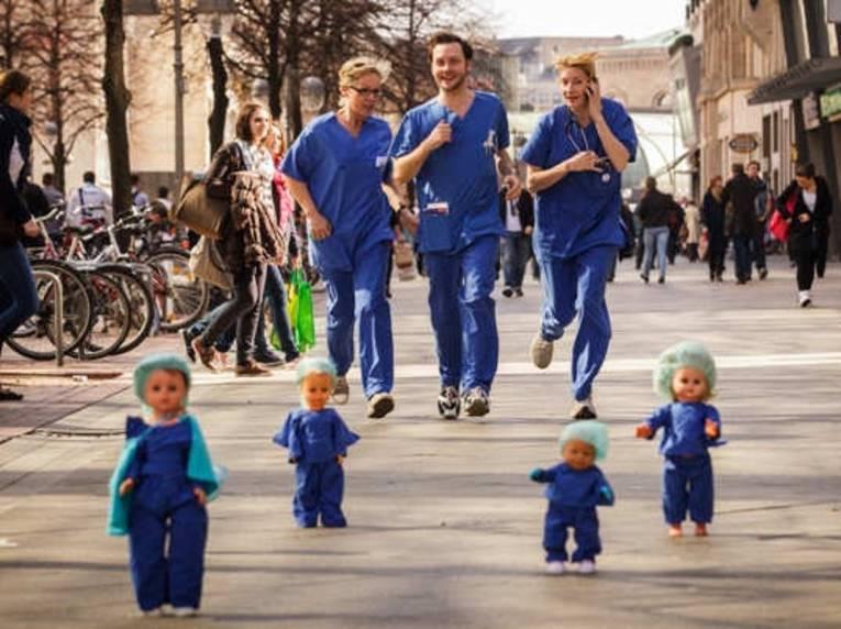 Zwei Frauen und ein Mann in blauer OP-Kleidung laufen durch die hannoversche Fußgängerzone. Sie sind umringt von stehenden Kinderpuppen, die genauso gekleidet sind wie sie.