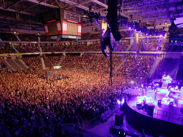 Buntes Schweinwerferlicht und Tausende Menschen: Eine Innenansicht der TUI Arena während eines Konzerts.