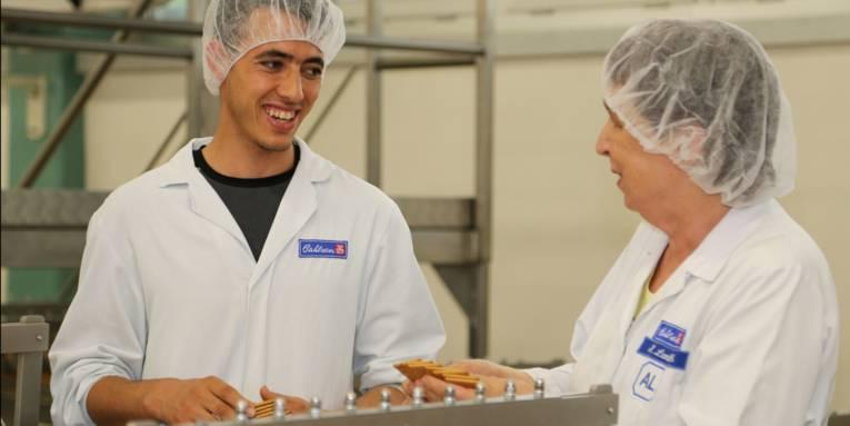 Zwei Personen an einem Keksproduktionsband