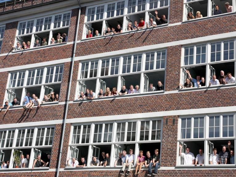 Viele Menschen schauen in einer Häuserfront aus den Fenstern.