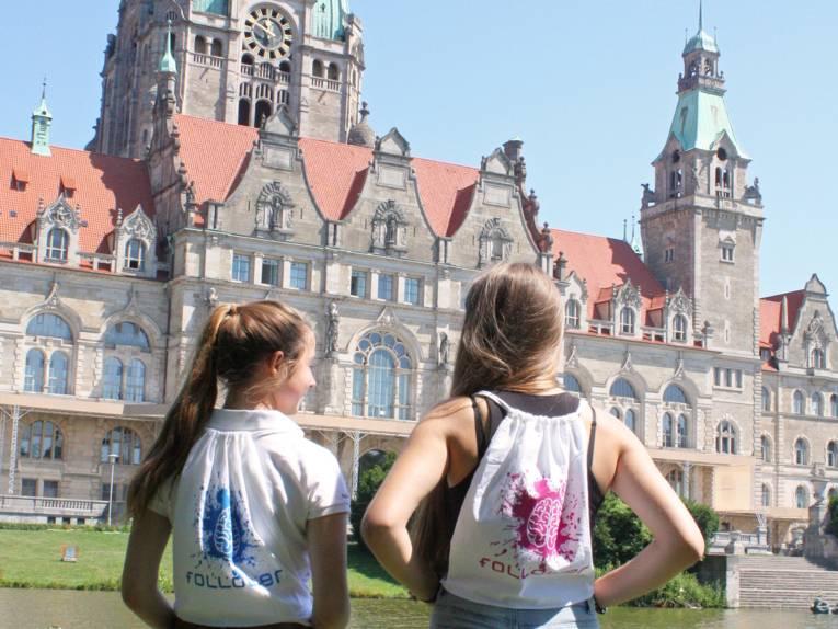 Zwei Mädchen vor einem altem schlossähnlichen Gebäude.